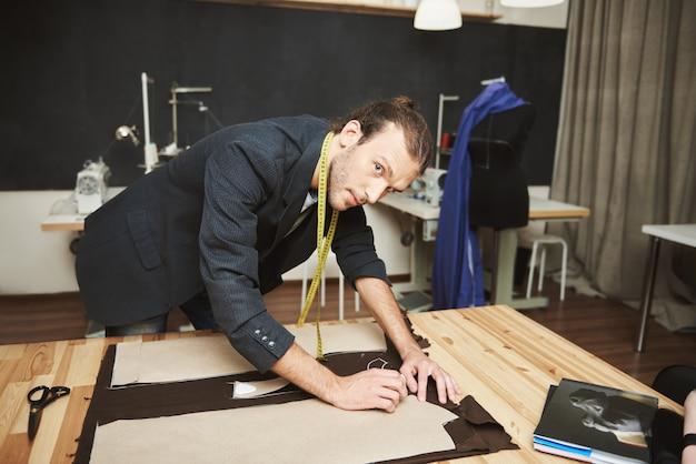 Художник в студии. крупным планом талантливый привлекательный молодой мужской модельер работает над новой зимней коллекцией, смотрит в камеру с расслабленным выражением, собирается вырезать части платья.