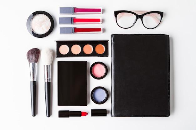 Декоративная косметика очки и блокнот на белом фоне