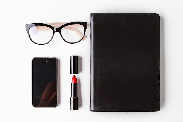 赤い口紅メガネ電話と白い背景の上のノート