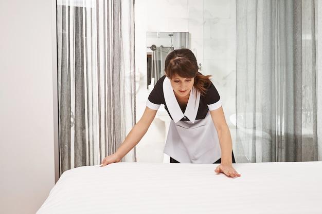 ベッドを作るメイドの制服を着た女性。新しい毛布ときれいなホテルの部屋を着て、場所を逃さず、訪問者が素敵な場所での滞在を楽しむことができるように最善を尽くしている女性のハウスクリーナーの肖像画