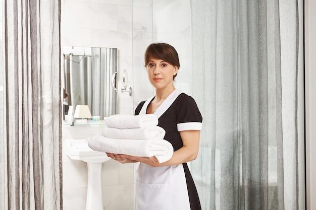 サー、私はバスルームに余分なタオルを置きます。落ち着いて真剣な表情でドアの近くに白いホテルのタオルでホテルで仕事をしているメイドの制服を着た女性の肖像画
