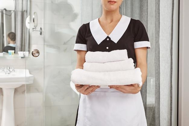 すべてが新鮮で清潔です。白いタオルのパックを保持しているメイドの制服を着たハウスクリーナーの肖像画をトリミングしました。従業員は顧客が注文したものをすべて自分のホテルの部屋に持ってきました