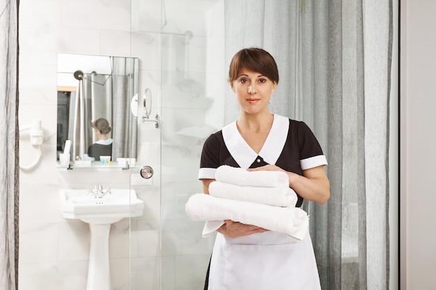 私たちはあなたが私たちのホテルで素晴らしい時間を過ごすことを保証します。メイドとして働いて、バスルームの近くに立って見つめながらタオルを保持している快適な白人女性の肖像画。シャワーの近くに置いた