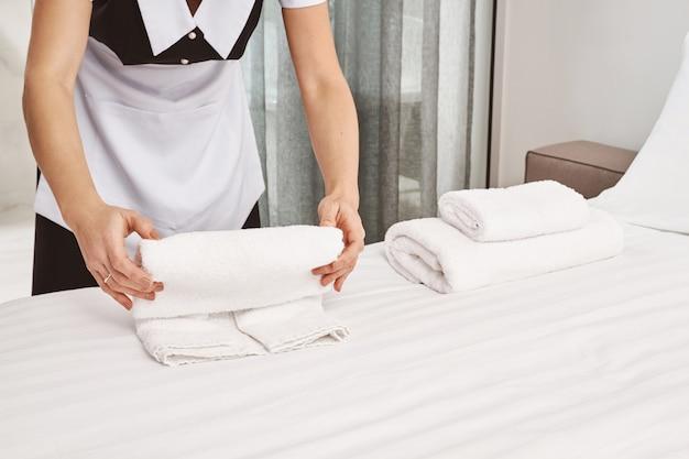 寝室を掃除し、クライアントが移動するためのすべての準備をしている間にベッドでタオルを転がしているハウスクリーナーのトリミングされた肖像画は、部屋をすっきりときれいに見せます。彼女のベストを尽くして当番メイド