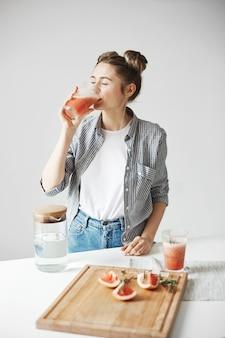 白い壁にグレープフルーツデトックススムージーを飲む笑顔のパンと美しい女性。健康的な食事の栄養