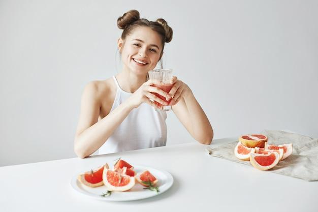 白い壁に健康的なデトックスフレッシュなグレープフルーツのスムージーとガラスを保持しているテーブルに座って笑って幸せな美しい女。