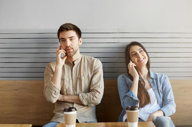 Двое молодых людей в ссоре сидят рядом друг с другом в столовой, смотрят в сторону, пьют кофе и разговаривают по телефону.