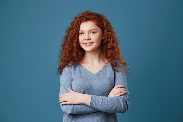 幸せでうれしそうな表情で見て、赤毛の髪と灰色のシャツの交差手でそばかすのある美しい学生の肖像画を間近します。