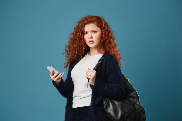 Несчастная красивый рыжий студент женщина с веснушками, держа телефон с нервным взглядом, после разговора с учителем о сдаче экзамена.