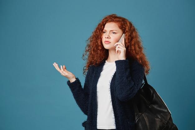 Портрет молодой красивой рыжеволосой женщины с вьющимися волосами и веснушками, говорящей по телефону с циничным лицом, спорящей с подругой об экзаменах.