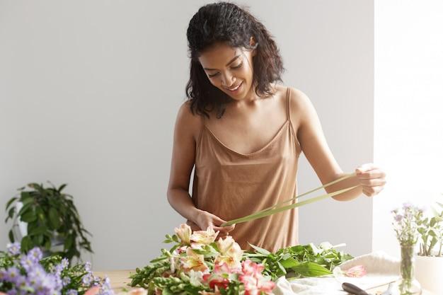 白い壁に花を保持している持株リボンの笑みを浮かべて陽気なアフリカ女性花屋。