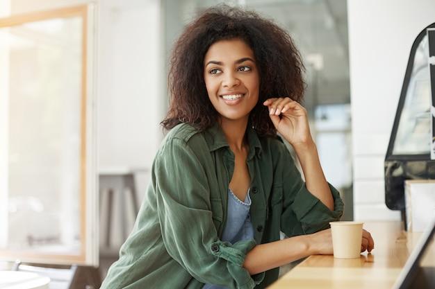 Сидеть молодого красивого африканского студента женщины отдыхая ослабляя в кофе кафа усмехаясь выпивая.