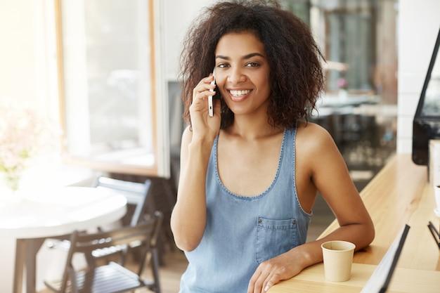 Говорить счастливой жизнерадостной красивой африканской женщины усмехаясь на телефоне сидя в кафе.