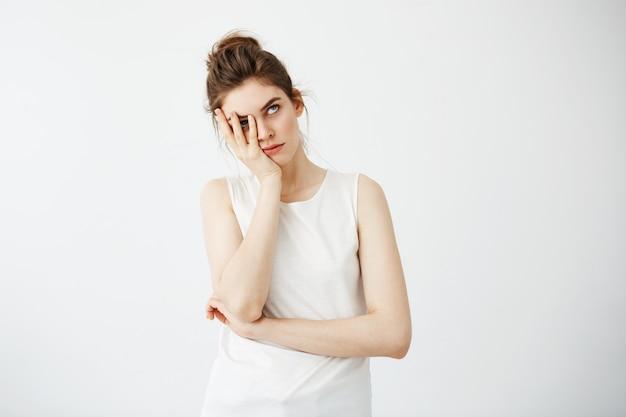 疲れた若いきれいな女性の手の後ろに顔を隠して退屈。