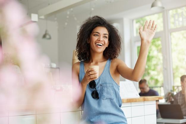 Счастливый красивая африканская женщина, сидя в кафе, улыбаясь, смеясь, приветствие пить кофе.