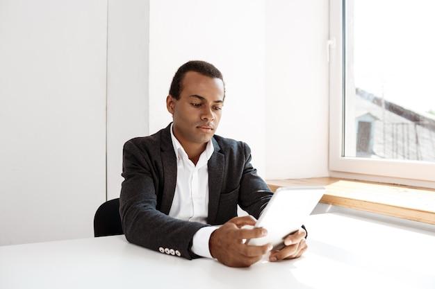 Молодой успешный бизнесмен, глядя на планшет, сидя на рабочем месте