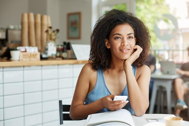 Мечтательный красивая женщина студент, сидя в кафе с книгами и журналами, улыбаясь, держа телефон мышления.