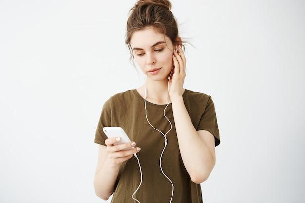 Молодая красивая женщина с плюшкой, улыбаясь, глядя на телефон прослушивания музыки в наушниках на белом фоне.