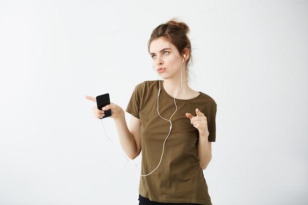 Музыка шальной жизнерадостной молодой женщины танцуя слушая в наушниках над белой предпосылкой.