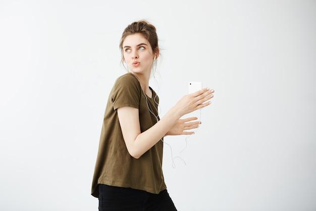 クレイジー陽気な若い女性が白い背景の上にヘッドフォンで音楽を聴いて歌って踊る。