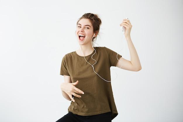 Музыка шальных жизнерадостных танцев молодой женщины поя слушая в наушниках над белой предпосылкой.