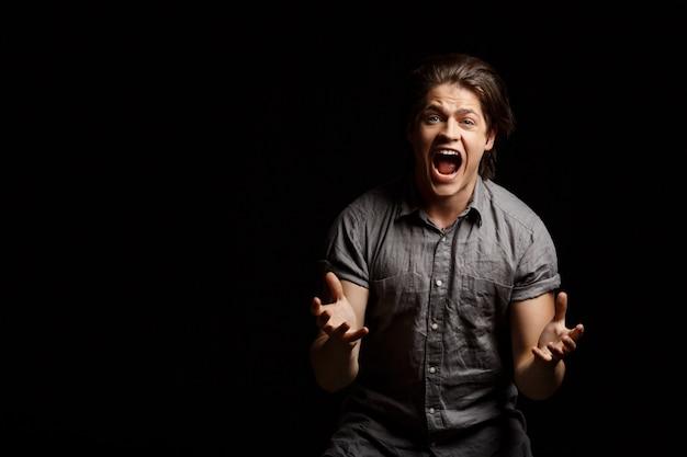 失望した若いハンサムな男が身振りで示す、叫ぶ