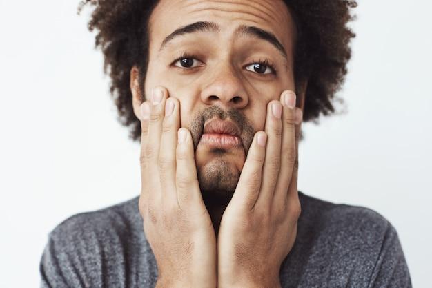 Закройте вверх по портрету расстроенного и утомленного молодого африканского человека хватая его лицо и щеки с руками. трудолюбивый студент в конце дня или жертва автомобильной аварии без страховки