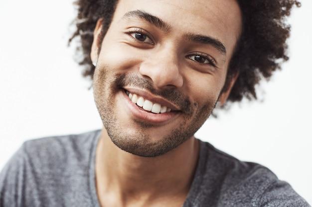笑みを浮かべてハンサムな陽気なアフリカ人の肖像画を間近します。
