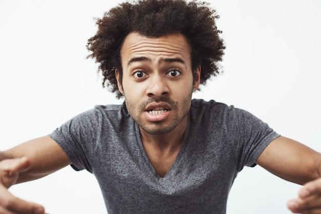 Веселый африканский человек, делая смешное лицо дурачиться.
