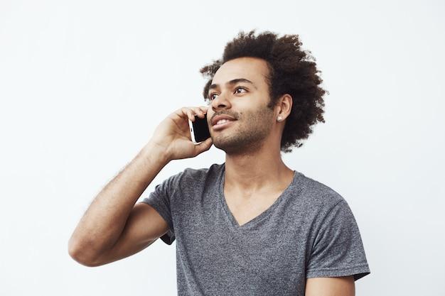 電話で話している笑顔の肯定的なアフリカ人。