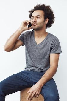 座っている電話で話している若いアフリカ人。