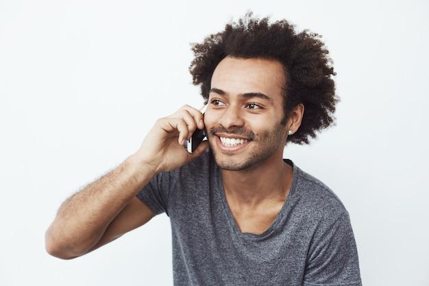 電話で話して笑っている陽気なアフリカ人。