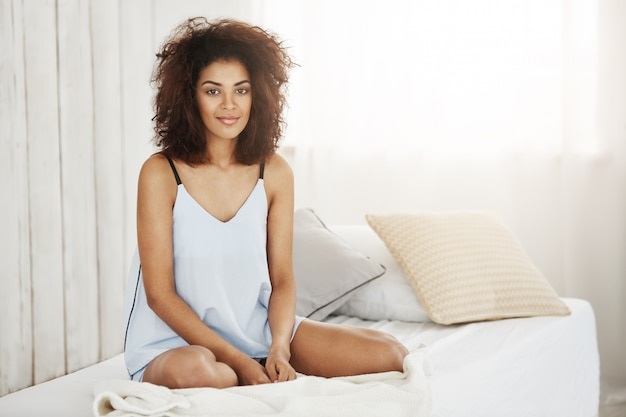Красивая африканская женщина в одежде для сна сидя на кровати дома усмехаясь.