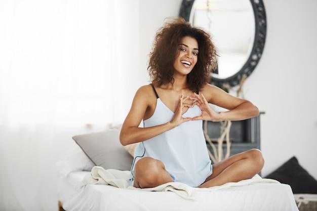 Красивая африканская женщина в одежде для сна усмехаясь показывая форму сердца сидя на кровати дома.