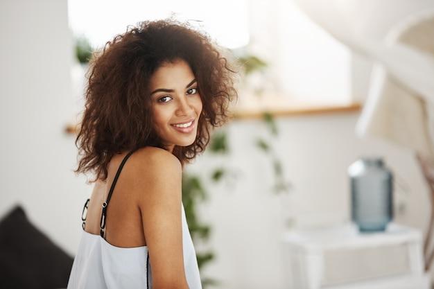 Портрет красивой африканской женщины улыбается. спальня фон.