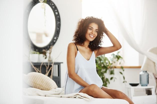 Молодая нежная африканская женщина в одежде для сна сидя на кровати дома усмехаясь.