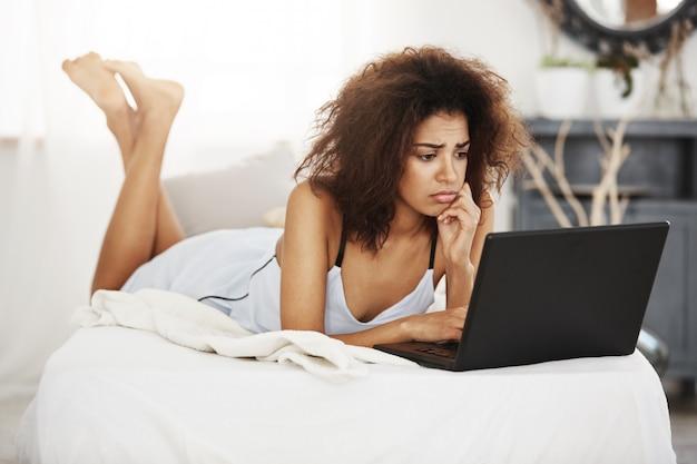 Расстроен красивая африканская женщина в пижамы, глядя на ноутбук, лежа на кровати у себя дома.