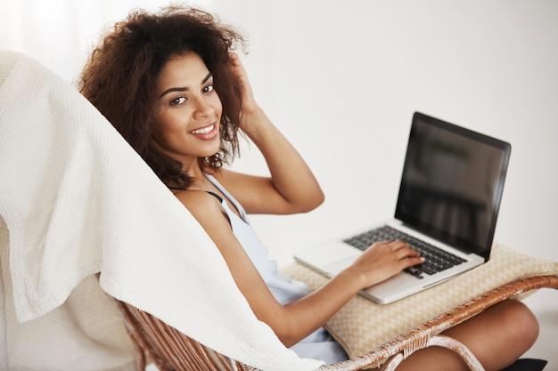 自宅の椅子にラップトップで座っている笑顔パジャマで美しいアフリカ人女性。