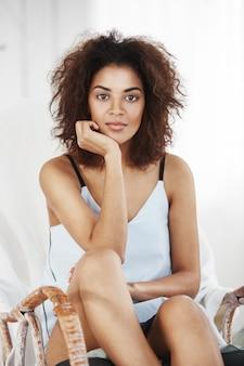 Портрет нежной красивой африканской женщины в отдыхать пижамы сидя в стуле дома.