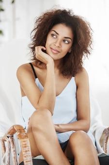 Портрет мечтательной красивой африканской женщины в усаживании пижамы усмехаясь думая сидеть в стуле дома.