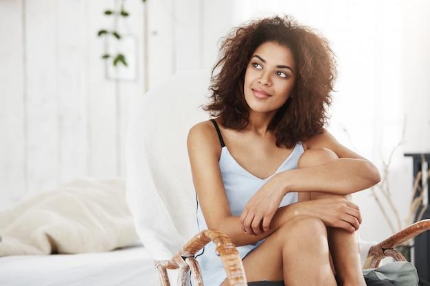 Портрет мечтательной красивой африканской женщины в усаживании одежды для сна усмехаясь в стуле дома.