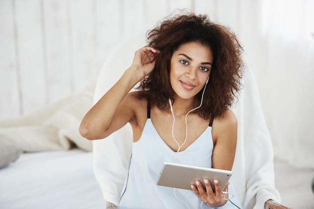 の上に座ってヘッドフォンで音楽を聴いて笑っているパジャマで若いアフリカ人女性。