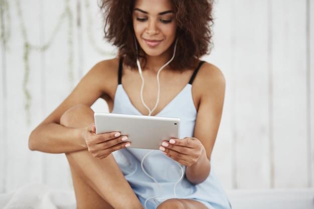 ベッドの上に座ってヘッドフォンで音楽を聴くタブレットを見て笑顔のパジャマで美しいアフリカ人女性。
