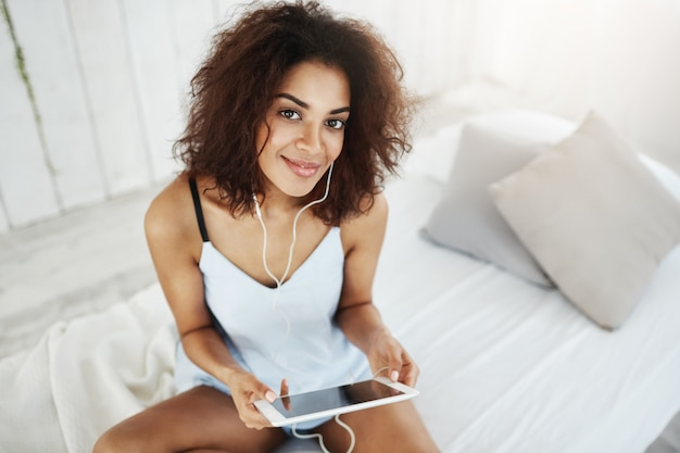 ベッドの上に座ってヘッドフォンで音楽を聴いて笑っているパジャマで美しいアフリカ人女性。