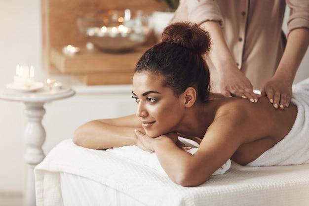 Красивая африканская женщина усмехаясь наслаждающся массажем в спа-курорте.