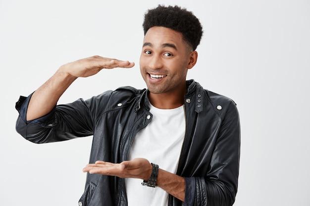 Изолированный портрет жизнерадостного молодого красивого чернокожего человека с афро прической в белой футболке и кожаной куртке держа коробку среднего размера в руках, смотря в камере с счастливым выражением стороны.