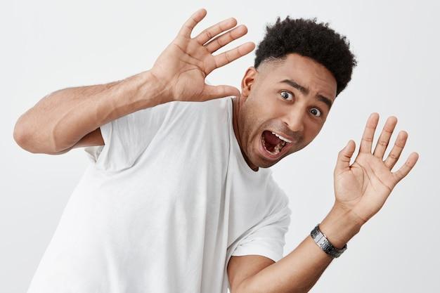 Закройте вверх изолированный портрет смешного молодого выглядящего богом привлекательного человека смуглой кожи с афро прической в модной белой футболке кричащей, будучи испуганным незнакомцем на улице.