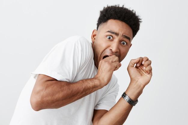 Эмоции людей. закройте молодого красивого темнокожего американского парня с афро прической в белой футболке, держащей руки около лица с испуганным выражением, смотря фильм ужасов ночью.