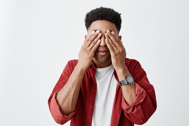 暗い肌の男の服の目の肖像画を手で閉じ、長い間オフィスでラップトップコンピューターで作業した後リラックスしようとしています。頭痛がして疲れている男。