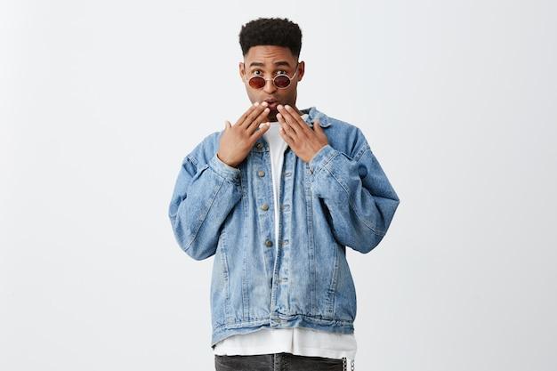 Крупным планом молодой темнокожий человек с афро прически в стильный наряд с солнцезащитные очки рот одежды с руками с удивленным выражением, видя друга из школы на улице.